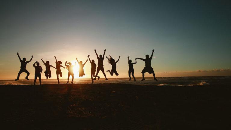 Fröhliche Menschen vor Sonnenuntergang